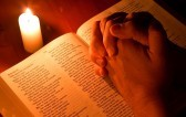 7234699-bibbia-a-lume-di-candela-con-mani-piegate-in-preghiera
